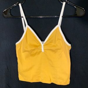 Mustard yellow crop top with white straps.